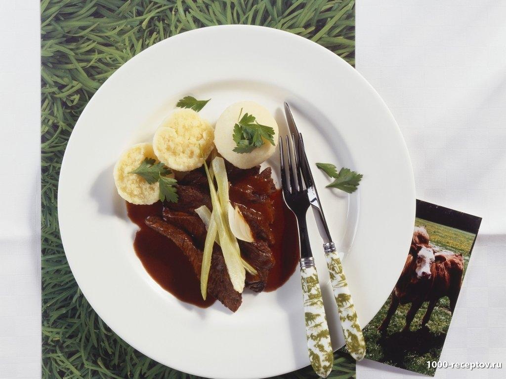 Тушеная говядина с картофельными клецками на тарелке