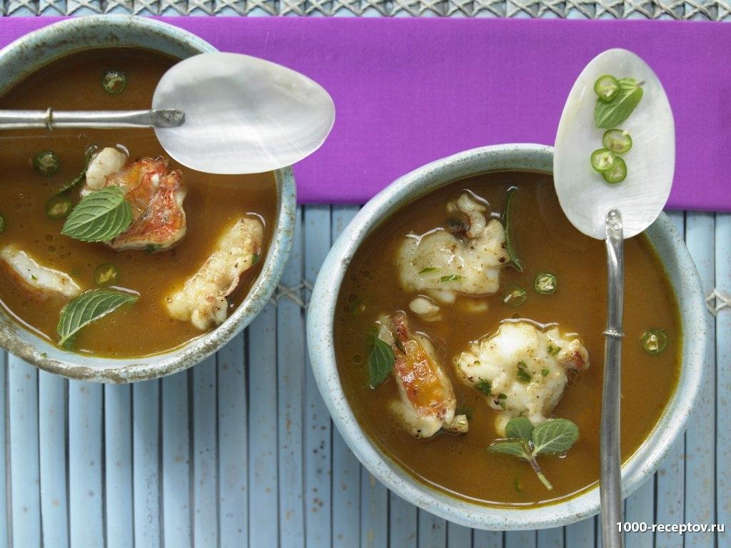 Кокосово-томатный суп с омарами, имбирем и перцем чили в тарелке
